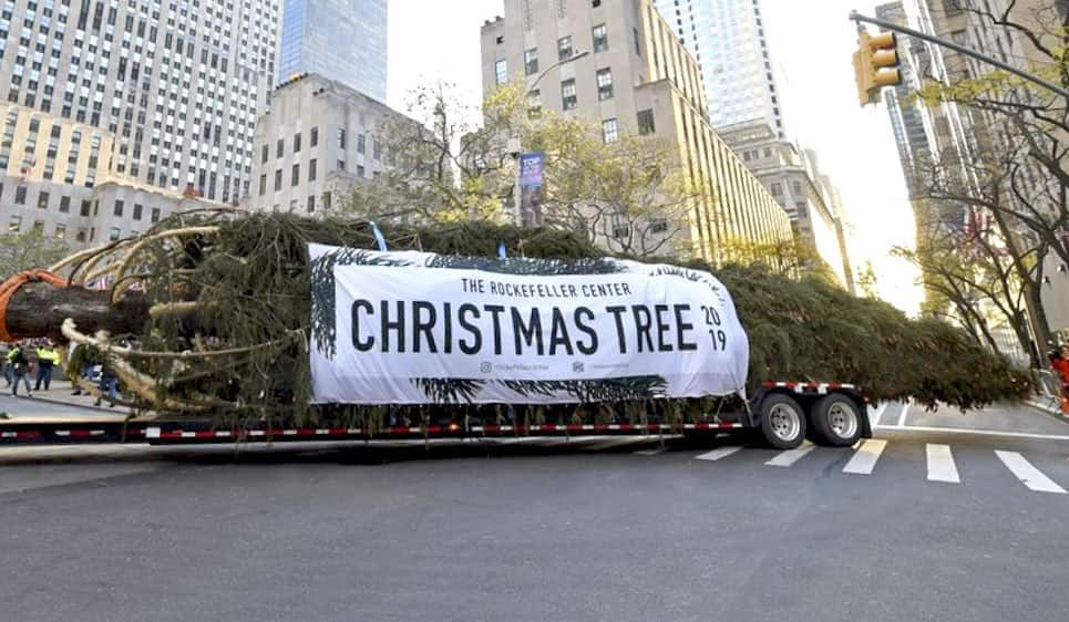 The 2019 Rockefeller Center Christmas Tree arrives with the Custom Banner produced by National Flag and Display.