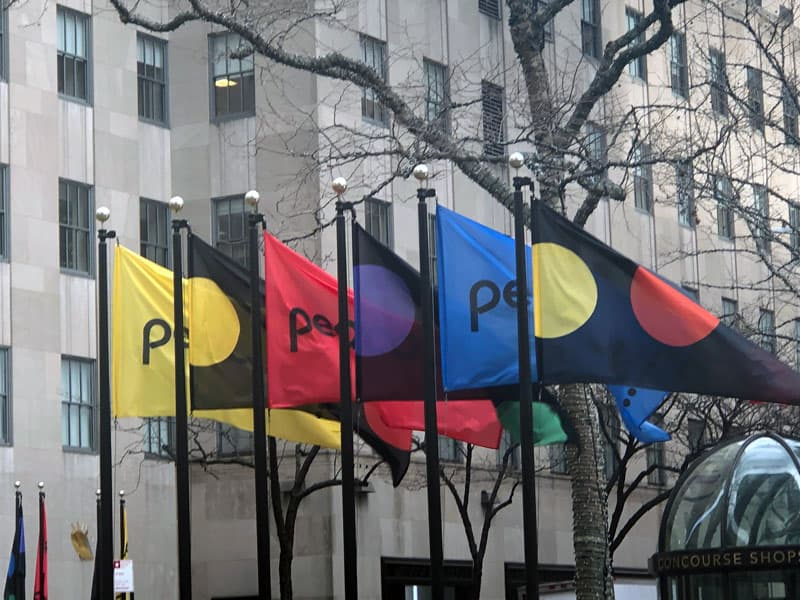 National Flag and Display produces the custom flags at Rockefeller Center for NBCUniversal's announcement of their new Peacock streaming service on January 16, 2020.
